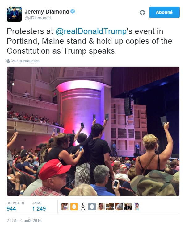 Traduction: Des protestataires au meeting de Donald Trump à Portland, Maine se lèvent et brandissent des copies de la Constitution pendant que Trump parle.